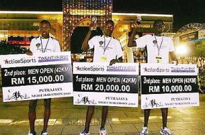 James Tallam (L) and Alex Melly (C) shows off their winnings at a marathon in Indonesia
