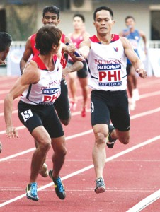 Anchorman Bagsit receives the baton from Alejan in their golden performance at the 2013 SEA Games. (Photocredits: KJ Rosales)